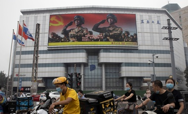 Residents wearing masks pass by a Chinese military propaganda display