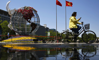 A woman rides a bicycle past a globe structure on display outside a bank in Beijing,