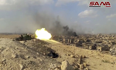 a Syrian army tank firing during a battle against Islamic State militants in Deir el-Zour