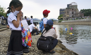 Saki Morioki, 5 years old, prays as paper lanterns float along the Motoyasu River in front of the Atomic Bomb Dome