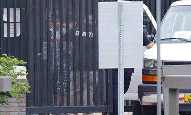 Authorities move immigrant children into a van from a youth holding facility