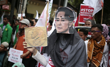A Muslim woman wears a mask of  Aung San Suu Kyi