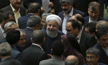 Iranian President Hassan Rouhani, surrounded by a group of lawmakers, leaves a session of parliament, in Tehran