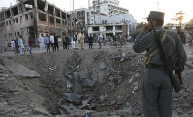 Afghan security forces stand next to a crater created by a massive explosion in Kabul