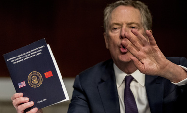 U.S. Trade Representative Robert Lighthizer holds up a document, Economic and Trade Agreement Between the United States of America and the People's Republic of China Phase One