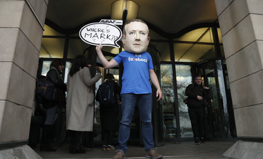 An activist wearing a Facebook CEO Mark Zuckerberg mask stands in front of Portcullis House in Westminster