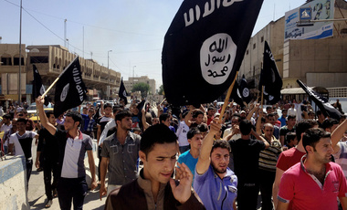 demonstrators chant pro-Islamic State group slogans as they carry the group's flags