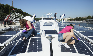 Crew members of the Energy Observer, a former race boat turned into a autonomous navigation with hydrogen, clean the solar panels of the boat in Paris