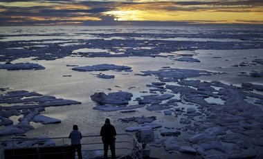 researchers look out from the Finnish icebreaker MSV Nordica as the sun sets over sea ice floating on the Victoria Strait