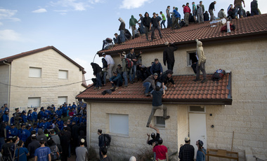 Settlers climb on a roof as Israeli police are evicting them the West Bank settlement of Ofra