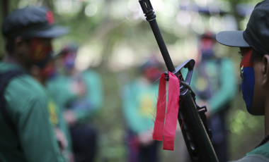red ribbon is tied to a firearm of a New People's Army guerrilla in the Philippines