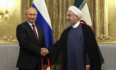 Iran's President Hassan Rouhani, right, shakes hands with Russian President Vladimir Putin