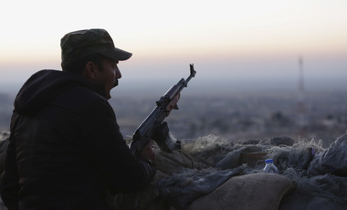 Kurdish fighter, known as a peshmerga, stands guard in Sinjar, Iraq
