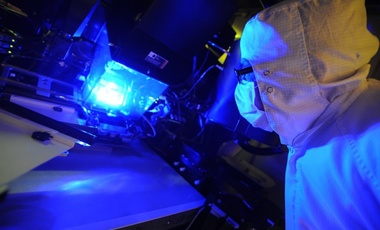 an operator inspects a photolithography tool used to manufacture these solar cells.