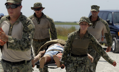 U.S. Navy Master-at-Arms Third Class Danielle Hinchliff, right, of Coastal Riverine Squadron 2, helps carry a mock wounded person