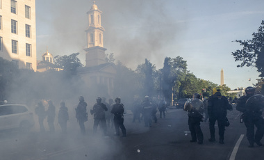 Tear gas floats in the air as a line of police move demonstrators away from St. John's Church