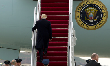 President Donald Trump walks up the stairs of Air Force One