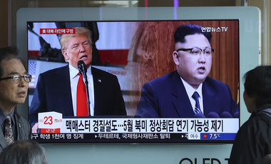 A TV screen shows North Korean leader Kim Jong Un, right, and U.S. President Donald Trump during a news program