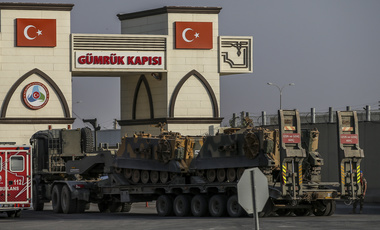 A Turkish forces truck transporting armored personnel carriers, crosses the border with Syria