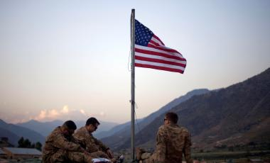 U.S. soldiers sit beneath an American flag