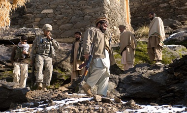 1st Lt. Kareem F. Hernandez, a New York and New Jersey resident and also 2nd Platoon Leader in Able Company, 2nd Battalion, 503rd Infantry Regiment (Airborne), talks on the radio while village elders and a Afghan National Policeman walk down the mountain during a patrol
