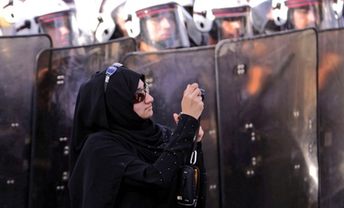 In this Jan. 18, 2012 file photo, an anti-government protester stands in front of riot police while photographing other demonstrators in Manama, Bahrain.