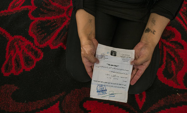"A 25-year-old Yazidi woman in Seeji, Iraq, who was held as a sex slave, holding a ""Certificate of Emancipation."""