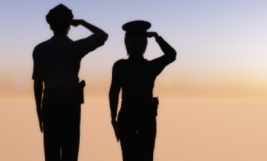 Two officers saluting at dawn.