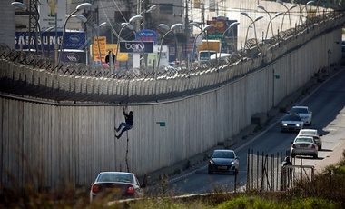 Palestinian man uses a rope to climb over a section of Israel's controversial separation barrier that separates the West Bank city of al-Ram from east Jerusalem (R) on February 24, 2016.