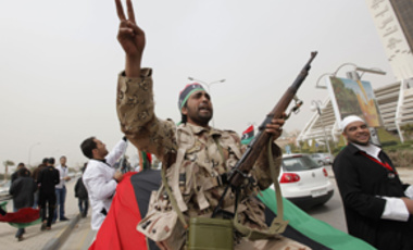 An armed Libyan rebel joins others on March 13, 2011, demanding the international community impose a no fly zone.