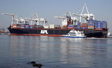 In this Dec. 8, 2011 photo, a ferry boat cruises in front of a container ship being loaded at the Port of Oakland in Oakland, Calif.