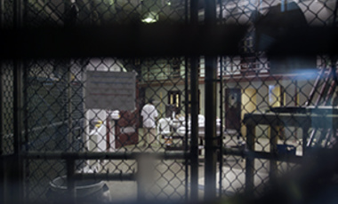 "In this photo reviewed by a U.S. Department of Defense official, a prisoner walks through a communal pod inside an area of the Guantanamo Bay detention center known as Camp 6, an area for prisoners who are considered ""highly compliant"" with the rules."