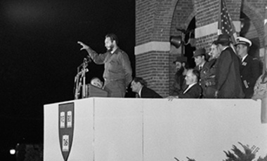 Cuban Prime Minister Fidel Castro gestures with his hand while speaking to an estimated crowd of 10,000 persons at Harvard University, Cambridge, Mass., April 25, 1959. Members of Castro's party stand behind the speaker. (AP Photo)