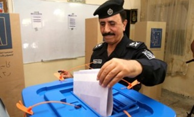 An Iraqi police officer casts his vote at a polling center in Baghdad, Iraq, Monday, April 28, 2014.