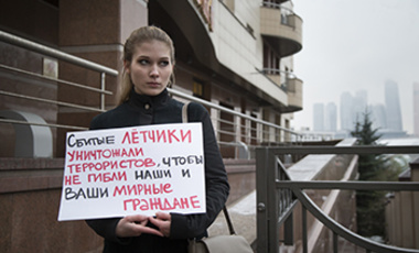 "A woman holds a poster as she pickets the Turkish Embassy in Moscow, Russia, Tuesday, Nov. 24, 2015. It reads: ""The pilots that were shot down were fighting terrorists to save your and our civilians."""