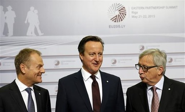 Friday, May 22, 2015 file photo of British Prime Minister David Cameron, center, as he stands with European Commission President Jean-Claude Juncker, right, and European Council President Donald Tusk
