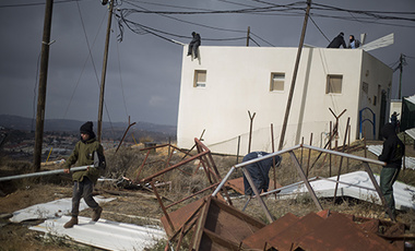 Jewish settler youth prepare barricades to block the entrance to a building in Amona, an unauthorized Israeli outpost in the West Bank, east of the Palestinian town of Ramallah, Thursday, Dec. 15, 2016.