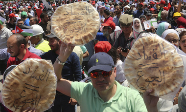 "Jordanian protesters shout ""bread"" in front of the Labour Union offices in Amman, Jordan Wednesday, June 6, 2018. ""Corruption equals hunger,"" is written in Arabic on loaves of bread. (AP Photo/Raad al-Adayleh)"