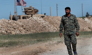 In this April 4, 2018 file photo, a U.S-backed Syrian Manbij Military Council soldier passes a U.S. position near the tense front line with Turkish-backed fighters, in Manbij, north Syria.
