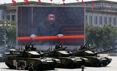 Chinese President Xi Jinping is displayed on a big screen in Beijing as Chinese battle tanks roll by during a Sept. 3, 2015 parade commemorating the 70th anniversary of Japan's surrender during World War II.