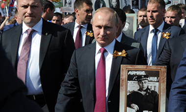 Russian President Vladimir Putin, center, holds a photograph of his father in a naval uniform, as he walks with people carrying portraits of relatives who fought in World War II, during the Immortal Regiment march in Red Square, in Moscow, May 9, 2016.