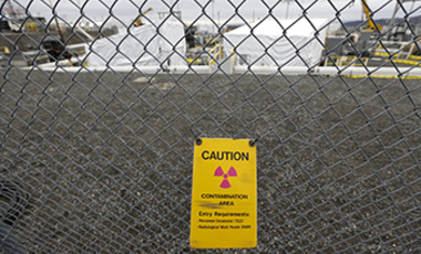 In this March 6, 2013 photo, a warning sign is shown attached to a fence at the 'C' Tank Farm at the Hanford Nuclear Reservation, near Richland, Wash.