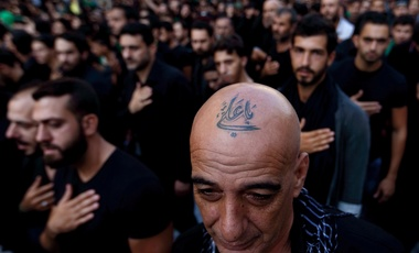 "In this Saturday, Oct. 24, 2015 file photo, a Lebanese Shiite supporter of Hezbollah with a tattoo on his head that reads in Arabic, ""Oh Ali"", beats his chest during the holy day of Ashoura, in the southern suburb of Beirut, Lebanon."