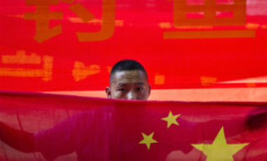A Chinese man holds a national flag during a protest outside the Japanese embassy in Beijing, Wednesday, August 15, 2012.