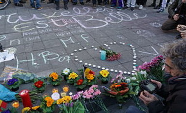 A memorial of chalk drawings, flowers, and candles for victims of the attacks in Brussels.
