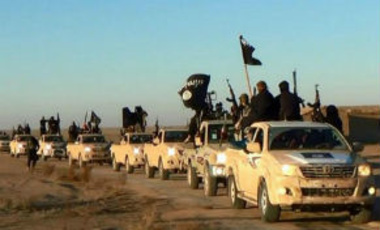 In this undated file photo, militants of the Islamic State group hold up their weapons and wave its flags on their vehicles in a convoy on a road leading to Iraq, in Raqqa, Syria.
