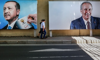 People walk past by an election poster of Turkey's president and ruling Justice and Development Party leader Recep Tayyip Erdogan, left, and Muharrem Ince, presidential candidate of the main opposition Republican People's Party, in Istanbul, Tuesday, June 19, 2018.
