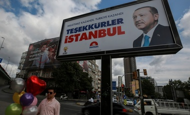 A day after the elections, people walk past a billboard with the image of Turkey's president Recep Tayyip Erdogan, in Istanbul, Monday, June 25, 2018.