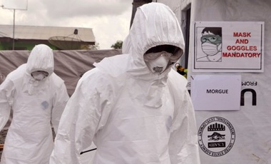 Health workers wearing Ebola protective gear remove the body of a man that they suspect died from the Ebola virus, at a USAID, American aid Ebola treatment center at Tubmanburg on the outskirts of Monrovia, Liberia, Friday, Nov. 28, 2014.
