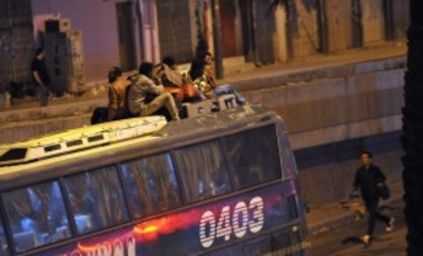 Illegal migrants sit on the roof of a police bus with their belongings on November 13, 2013 before being transferred to a center in the capital Riyadh ahead of their deportation (November 13, 2015).